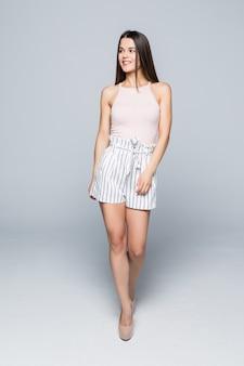 Volledige lengte van mooie jonge vrouw lopen en geïsoleerd op een witte muur.