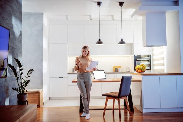 Volledige lengte van mooie kaukasische blonde jonge vrouw die op eettafel leunt, administratie houdt en slimme telefoon met behulp van. op tafel liggen papieren en laptop.