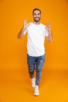 Volledige lengte van mooie man in t-shirt en spijkerbroek met ok teken terwijl staande, geïsoleerd op geel