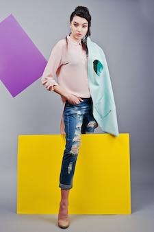 Volledige lengte van mooie meisjeszitting, houdend groen leeg reclamebord, over grijze achtergrond en gele en violette banner