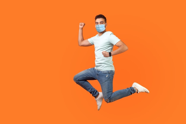 Volledige lengte van positief geïnspireerde brunette man met medisch masker in sneakers, denim outfit die in de lucht springt of snel snel rent. indoor studio-opname geïsoleerd op een oranje achtergrond, lege kopie ruimte