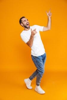 Volledige lengte van positieve man in t-shirt en spijkerbroek wijzende vingers omhoog terwijl staande, geïsoleerd op geel