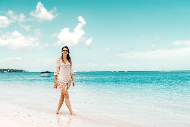 Volledige lengte van prachtige blanke vrouw in zomerjurk poseren op een strand.