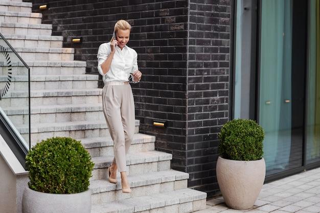 Volledige lengte van prachtige glamoureuze blonde glimlachende modieuze vrouw de trap af en praten aan de telefoon.