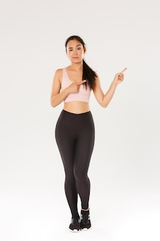 Volledige lengte van sceptische en twijfelachtige aziatische vrouwelijke brunette, meisjesatleet twijfelt, wijzende vingers rechtsboven, fronsend en kijkend met ongeloof, sportvrouw toont promo.