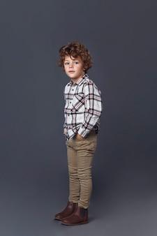 Volledige lengte van schattige krullende kleine jongen in casual kleding geïsoleerd op grijs
