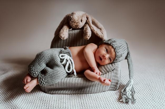 Volledige lengte van schattige pasgeboren jongen gekleed in gebreide broek en met gebreide muts op hoofd liggend in kleine fauteuil.