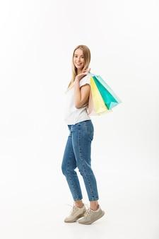 Volledige lengte van shopper vrouw met boodschappentassen permanent blij lachend en opgewonden in het volledige lichaam geïsoleerd op een witte achtergrond.