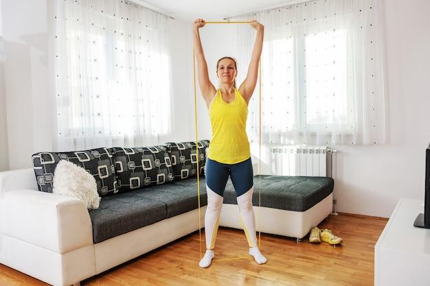 Volledige lengte van sportvrouw die zich thuis bevindt en machtsrubber uitrekt