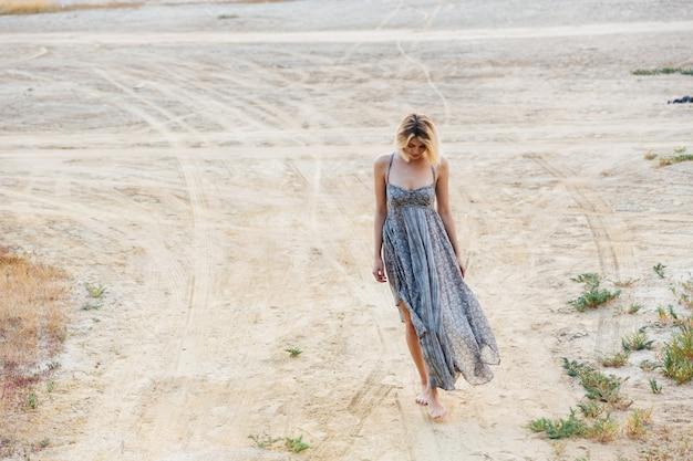 Volledige lengte van trieste mooie jonge vrouw die op de weg loopt