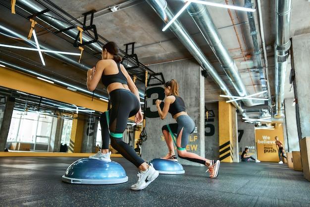 Volledige lengte van twee jonge atletische vrouwen in sportkleding die samen trainen met weerstandsfitnessbanden bij crossfit gym, squats doen en benen trainen. workout, sport, wellness en een gezonde levensstijl