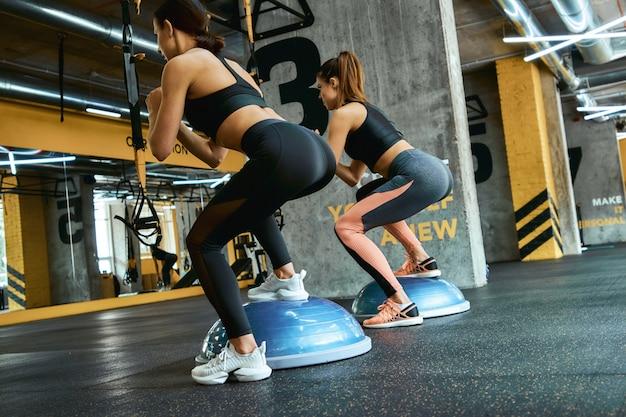 Volledige lengte van twee jonge atletische vrouwen in sportkleding die squats doen terwijl ze samen trainen in crossfit gym. training, training, actieve en gezonde levensstijl