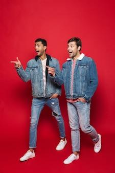 Volledige lengte van twee lachende jonge mannen lopen geïsoleerd over rode muur, praten