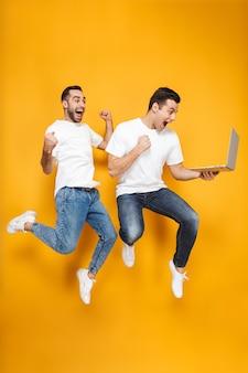 Volledige lengte van twee vrolijke opgewonden mannenvrienden die lege t-shirts dragen die geïsoleerd over gele muur springen, laptop gebruiken, creditcard houden