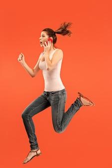 Volledige lengte van vrij jonge vrouw die telefoon neemt terwijl het springen tegen rode studioachtergrond.