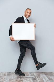 Volledige lengte van vrolijke afrikaanse jongeman die loopt en een whiteboard vasthoudt