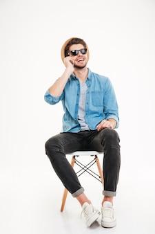 Volledige lengte van vrolijke jonge man in hoed en zonnebril die zit en praat op mobiele telefoon