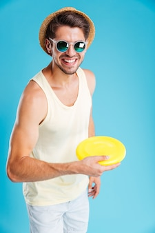 Volledige lengte van vrolijke jongeman die frisbeeschijf gooit throw