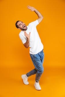Volledige lengte van vrolijke kerel in t-shirt en spijkerbroek die handen opheft terwijl hij staat, geïsoleerd op geel
