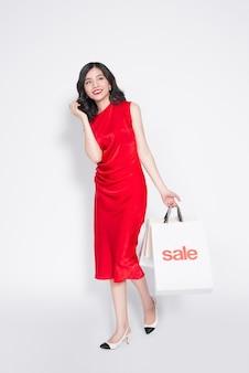 Volledige lengte van vrolijke modieuze aziatische vrouw die een rode jurk draagt met boodschappentassen