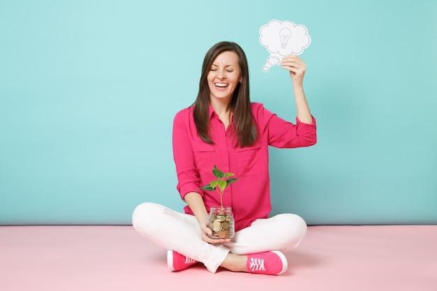 Volledige lengte van vrouw in roze shirt, witte broek zittend op de vloer met gouden munten in glazen pot