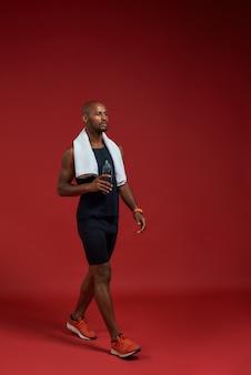 Volledige lengte van zelfverzekerde afro-amerikaanse man in sportkleding met handdoek op zijn schouders
