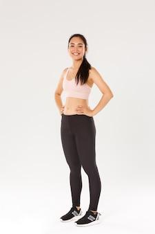 Volledige lengte van zweterig lachend fitnessmeisje, vrouwelijke athelte in actieve slijtage kijkt tevreden tijdens het trainen, training in de sportschool, tevreden met oefeningen, coach helpt perfect lichaam te krijgen, witte muur