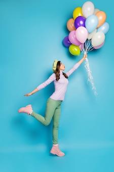 Volledige lengte verticale foto van gekke dame open mond houden veel luchtballonnen opstaan met wind dragen paarse trui baret pet groene broek laarzen geïsoleerde blauwe kleur muur