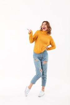 Volledige lengte vrolijke vrouw in sweater het stellen met wapen op heup hile wijzend en wegkijkend over witte muur