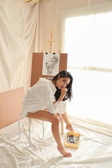 Volledige lengte vrouw kunstenaar in wit shirt denken iets tijdens het tekenen foto met potlood (vrouw levensstijl concept)
