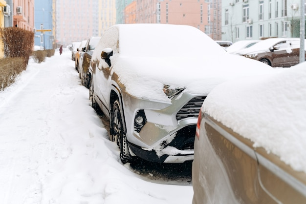 Volledige lengte weergave van de rij auto's onder de sneeuw na een sneeuwval. auto's op de besneeuwde parkeerplaats. besneeuwde winter en veel sneeuwconcept