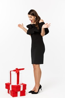 Volledige lengte weergave van vrouw in elegante jurk en rode lippen, verbaasd kijken, cadeaus ontvangen op kerstvakantie, staande met cadeautjes op witte achtergrond