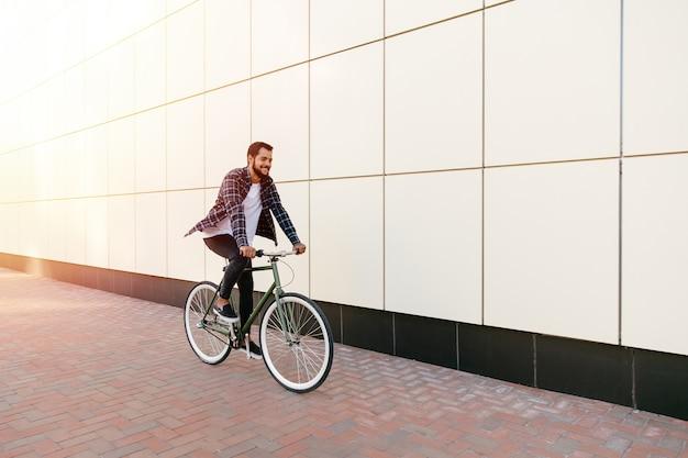 Volledige lengtefoto van de glimlachende jonge gebaarde mens die een fiets berijden op de stadsstraat.