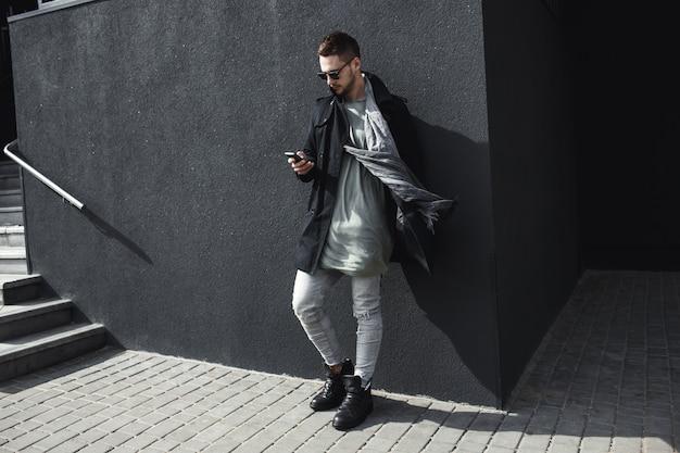 Volledige lengtefoto van de mens in laag het texting bericht buiten.