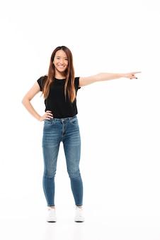 Volledige lengtefoto van gelukkige charmante aziatische vrouw in vrijetijdskleding die zich met uitgestrekte hand bevindt, wijzend met vinger, bekijkend camera