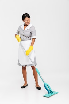 Volledige lengtefoto van gelukkige huishoudster in eenvormige schoonmakende vloer met zwabber