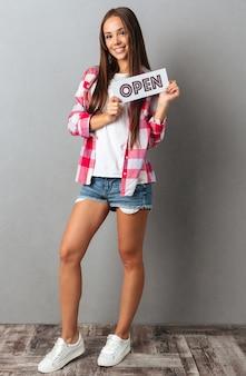 Volledige lengtefoto van glimlachende jonge donkerbruine vrouw die open teken houdt