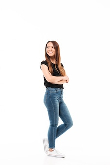 Volledige lengtefoto van jonge vrij chinese vrouw in zwarte t-shirt en jeans die zich met gekruiste handen bevinden, die opzij kijken