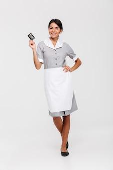 Volledige lengtefoto van vrij donkerbruine huishoudster die zich met hand op haar taille bevindt en creditcard houdt