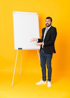 Volledige lengtezakenman die een presentatie op witte raad over geïsoleerde gele muur geven