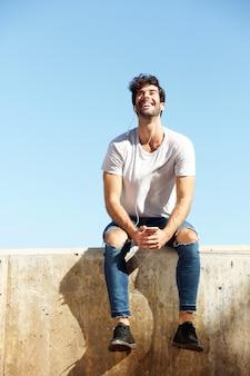 Volledige lichaam gelukkig man zit op betonnen muur met oortelefoons en mobiele telefoon