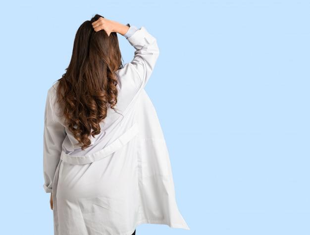 Volledige lichaam jonge artsenvrouw van achter het denken over iets