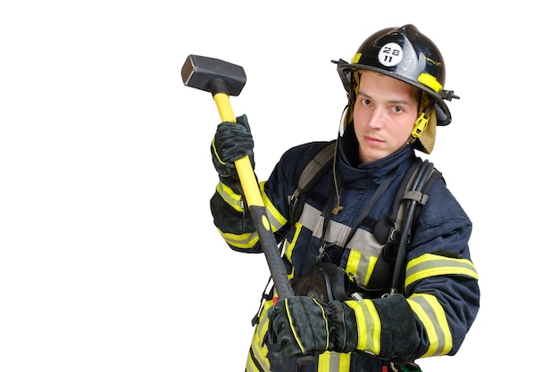 Volledige lichaam jonge dappere man in uniform, bouwvakker van brandweerman en volledig gezichtsmasker zwaait voorhamer