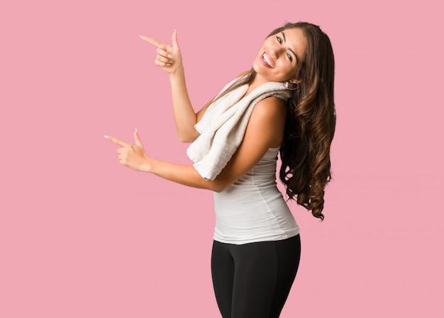 Volledige lichaam jonge fitness bochtige vrouw wijzend naar de kant met de vinger
