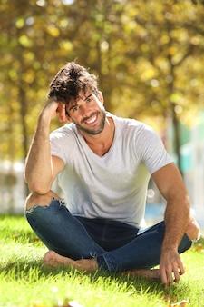 Volledige lichaam knappe man zit buiten in gras leunend hoofd aan kant