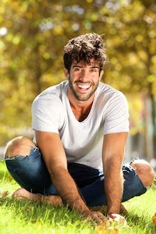 Volledige lichaam knappe man zit buiten in gras leunt naar voren lachen