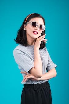Volledige lichaam van lachende aziatische vrouw gekleed in pin-up stijl jurk dragen brillen over blauw.