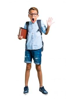 Volledige lichaam van student jongen met rugzak en bril met verrassing en geschokt.