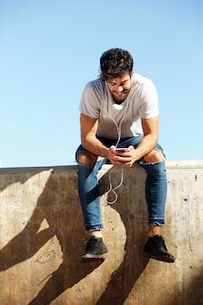 Volledige lichaam vrolijke man zit op betonnen muur met koptelefoon en mobiel