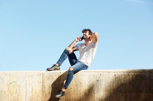 Volledige lichaam vrolijke man zittend op betonnen muur praten over slimme telefoon